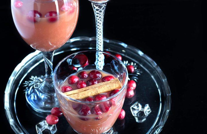 Cranberry, Orange & Cinnamon Cocktail in a glass with a cinnamon stick and fresh cranberries