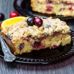 A piece of Cranberry Orange Crumb Cake with cranberries scattered around it in the table