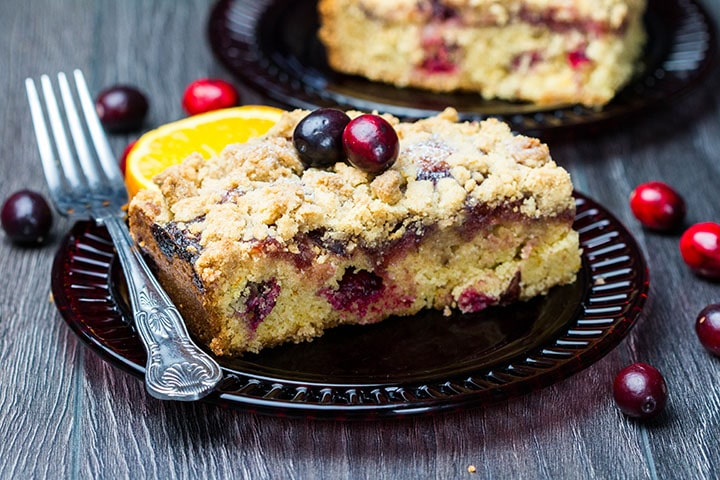 A piece of Cranberry Orange Crumb Cake with cranberries scattered around it on the table