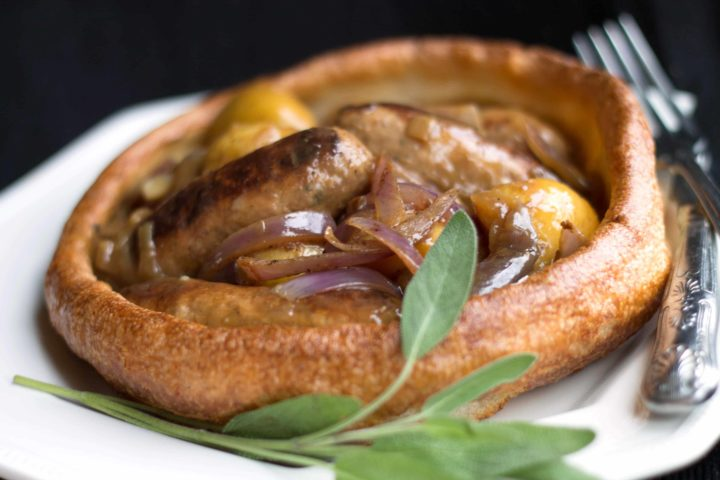 sausage and onion gravy served in a large Yorkshire pudding with cutlery on the side