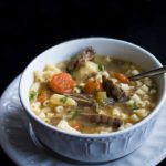 A bowl full of Slow Cooker Beef Brisket Soup with vegitables and small soup pasta added