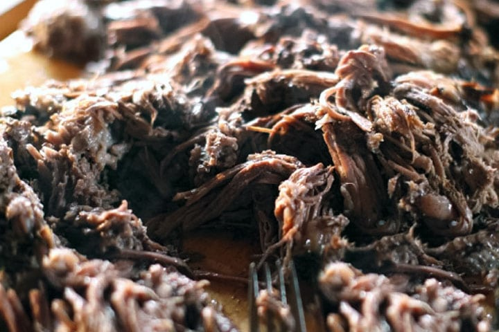 The Beef Brisket meat shredded with a fork