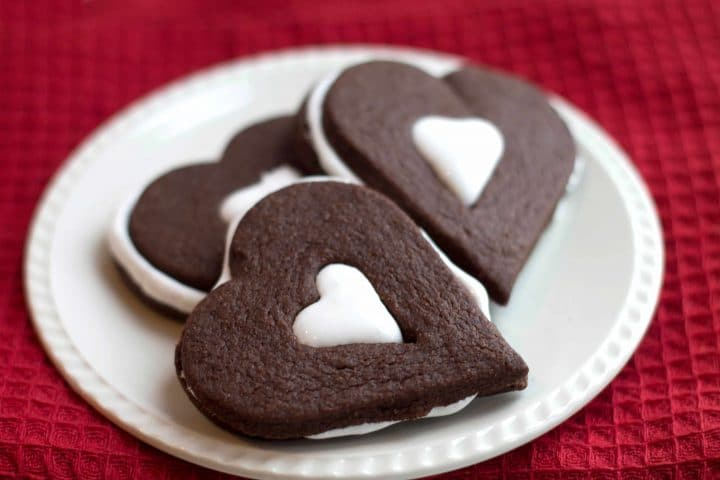 A plate with three heart shaped Chocolate Marshmallow Linzer Cookies on a white plate