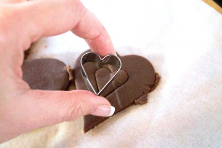 Cookie dough in a heart shape with a small cookie cutter cutting out the center of the heart