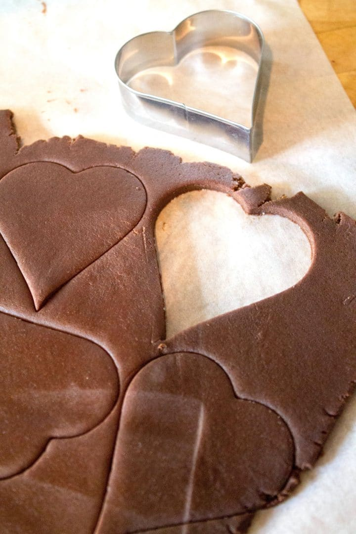 Chocolate cookie dough rolled out with a heart shaped cookie cutter and hearts cut out of the dough