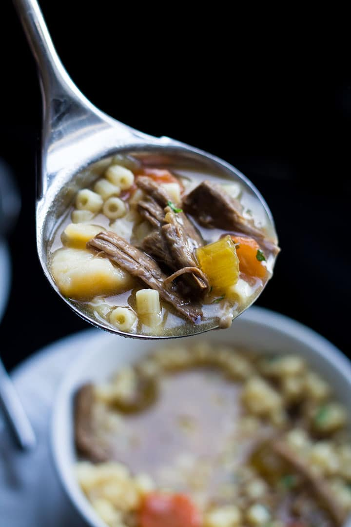 The Slow Cooker Beef Brisket Soup being ladled into a bowl