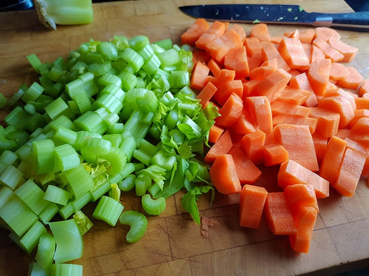 carrots and celery cut into bite sized peices on a cutting board with a knife in the background.