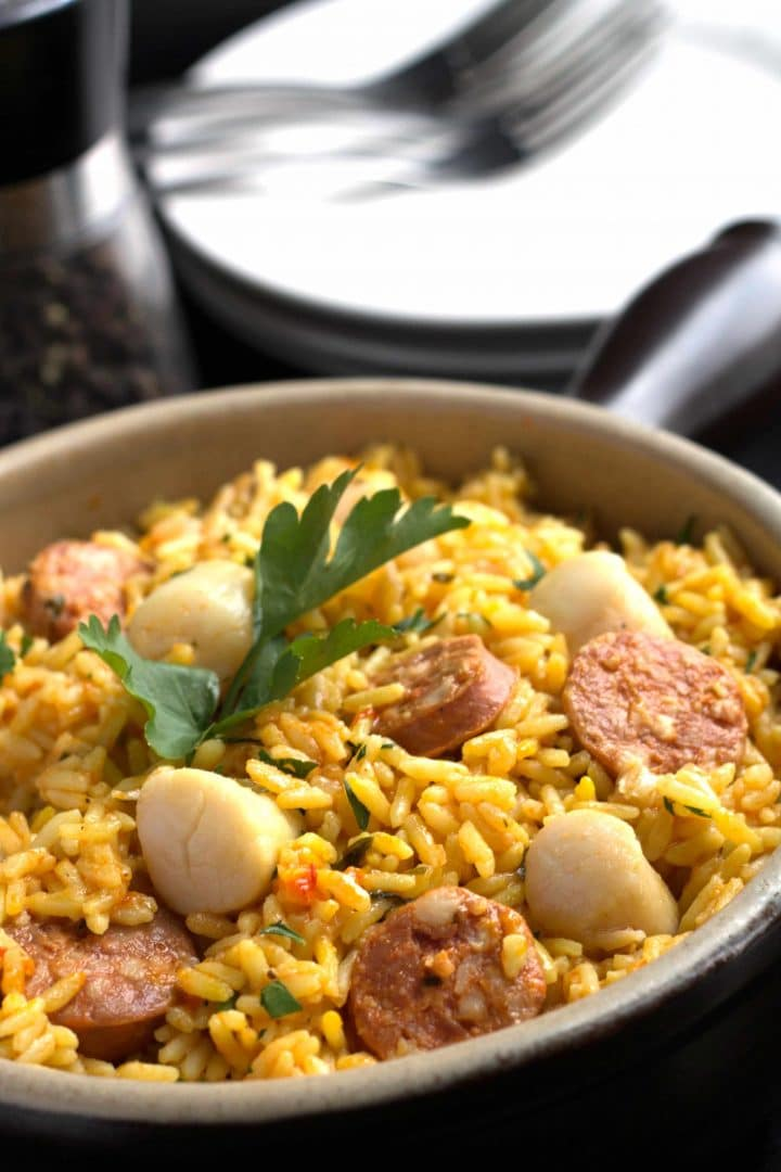 Easy Scallops & Chorizo Paella in a pan with parsley as garnish