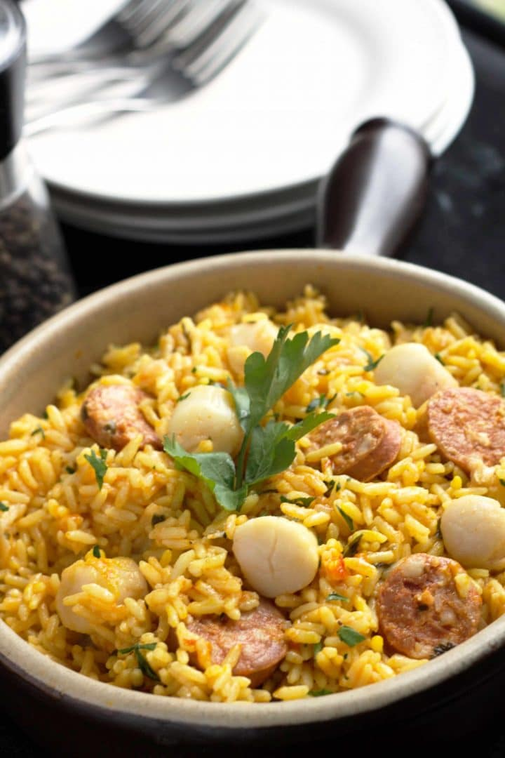 Easy Scallops & Chorizo Paella in a pan with dishes and forks on the table in the background