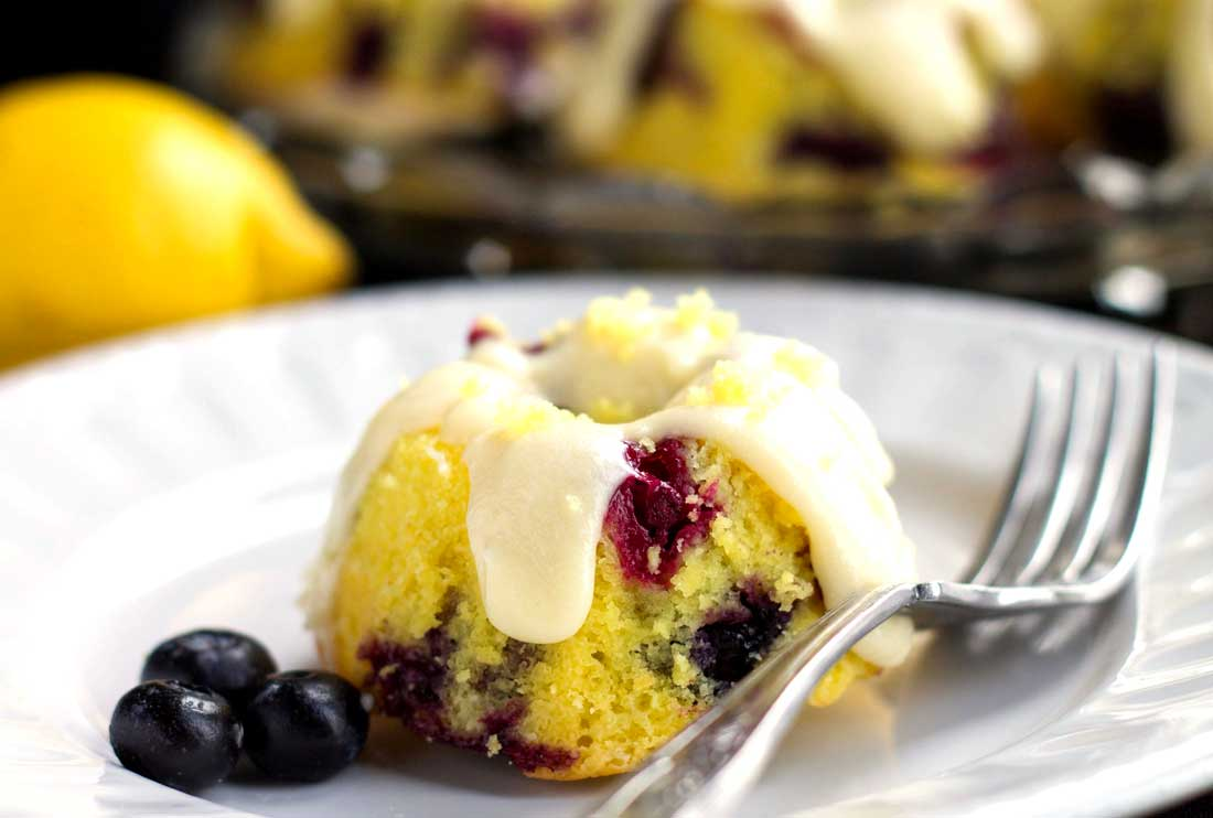 One frosted Lemon Blueberry Cake with blueberries and a fork next to it and more cakes and a lemon in the background.