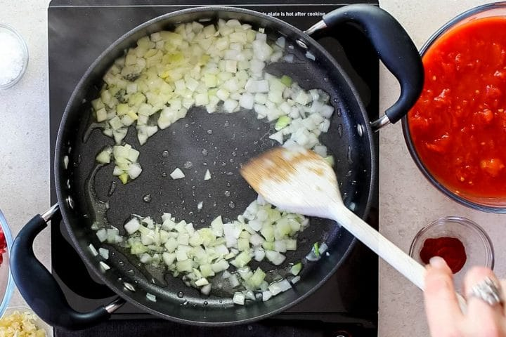A pan with onions cooking in olive oil