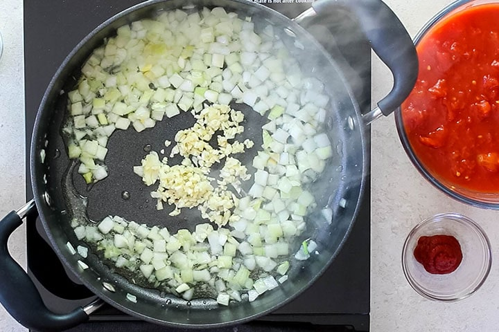 A pan with onions and garlic cooking in olive oil