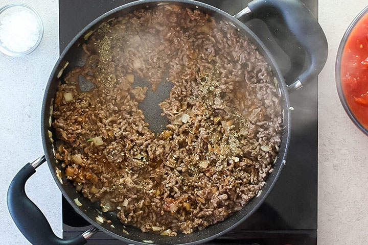 A pan with the oregano added to the ground beef