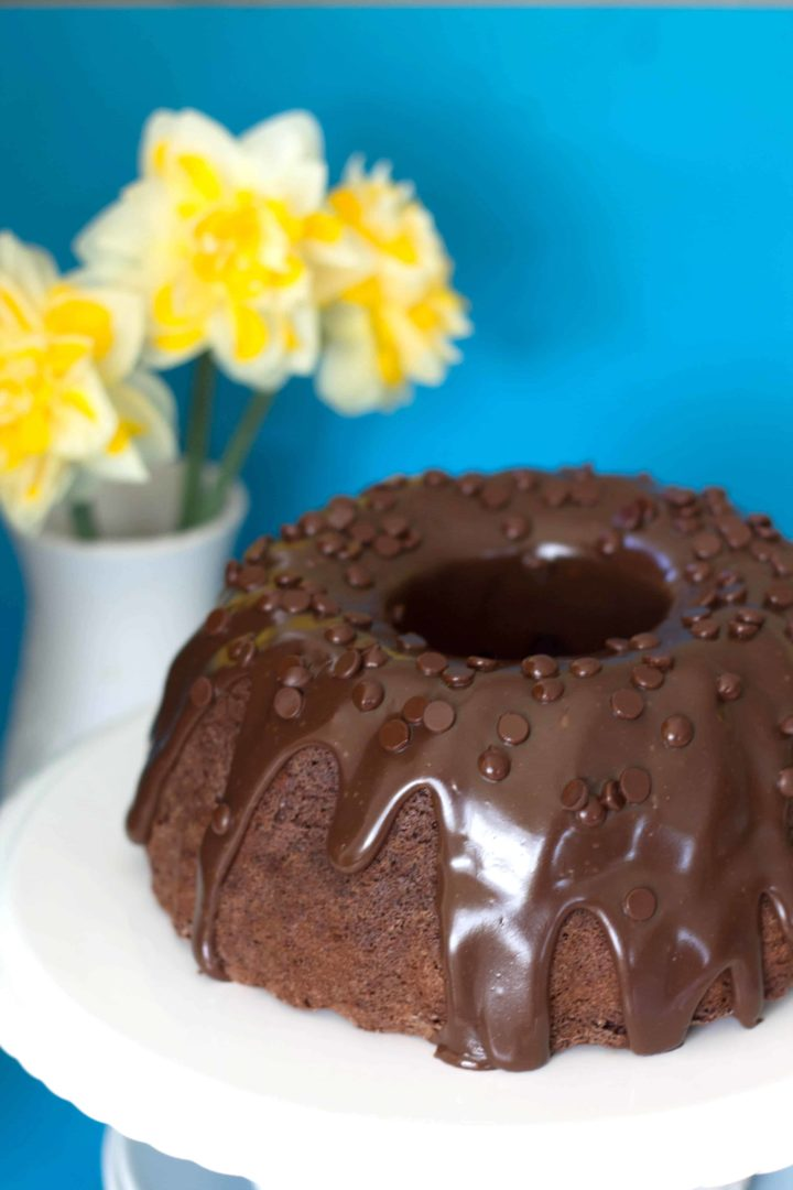 Double Chocolate Bundt Cake on a serving dish with a vase with yellow flowers in the background
