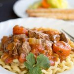 A plate of Italian Lamb Stew on a bed of pasta with a fork