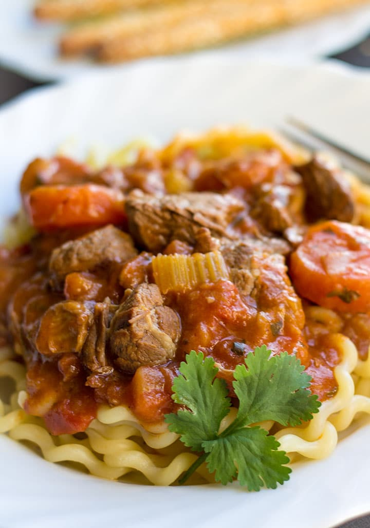 Italian Lamb stew on a bed of pasta on a decorative plate