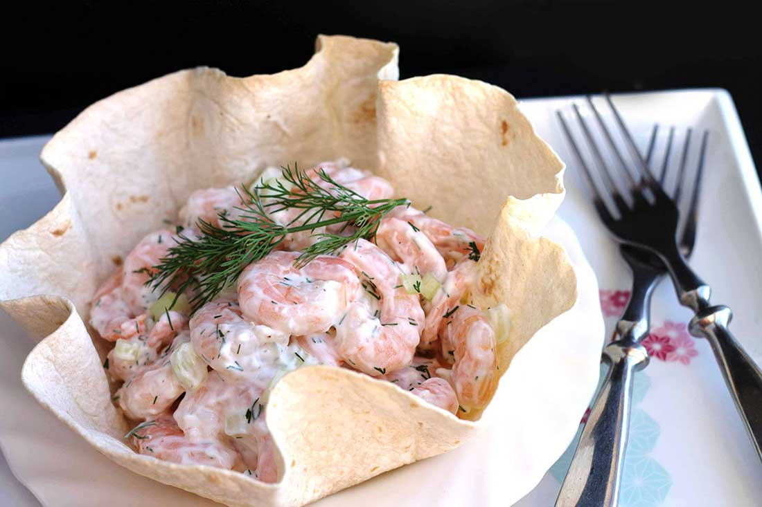 Shrimp salad in a tortilla bowl topped with dill and two forks on the plate next to it.