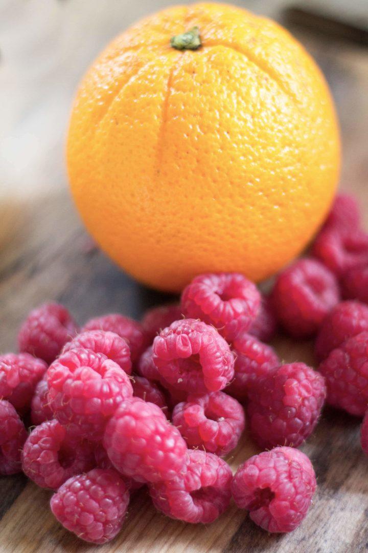 Raspberries and an orange