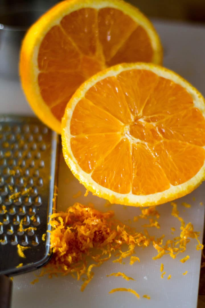 an orange cut in half with a grater and grated orange peel next to it