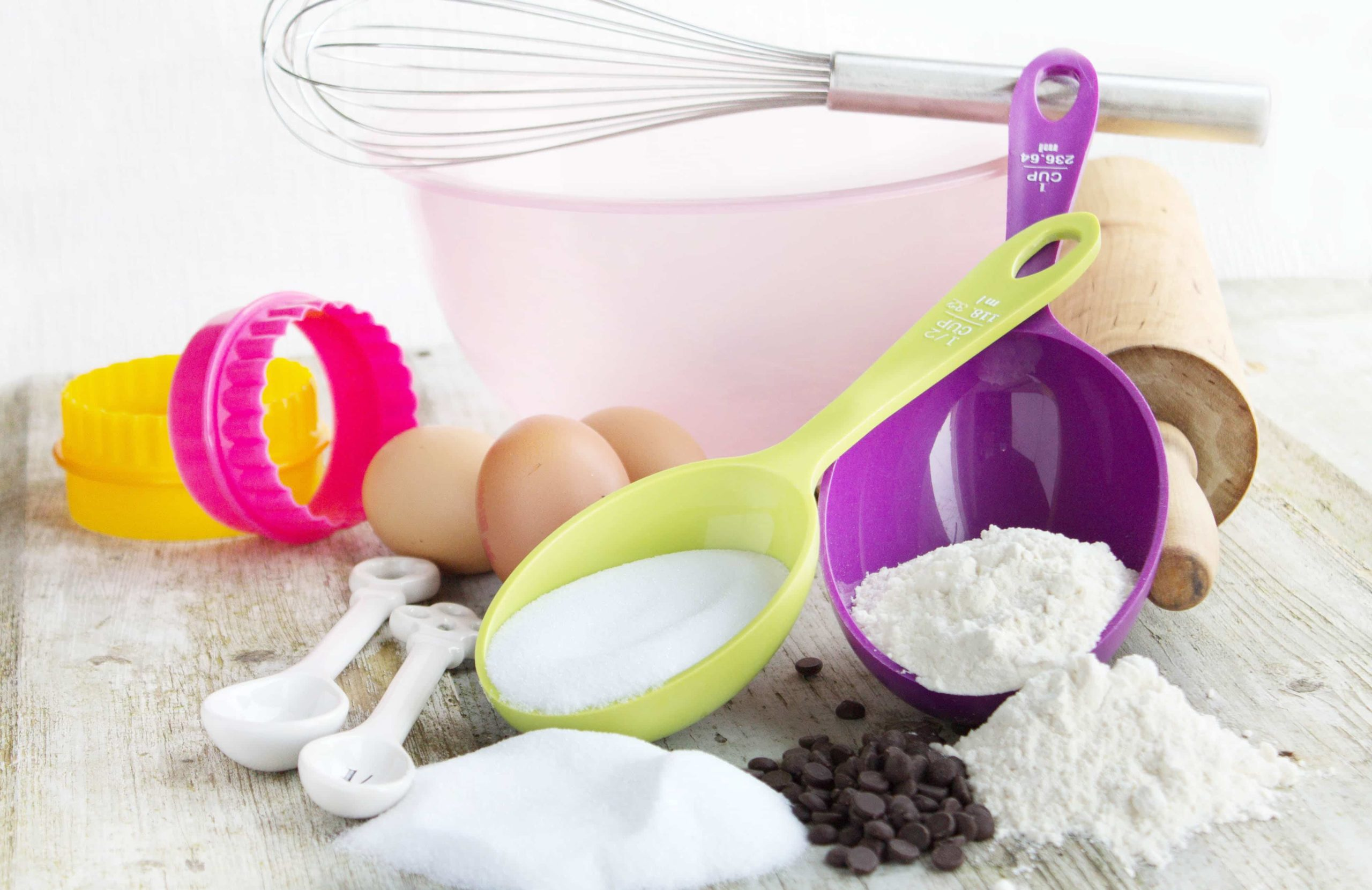 A plastic bowl, whisk, cookie cutters, measuring spoons and ingredients used for baking