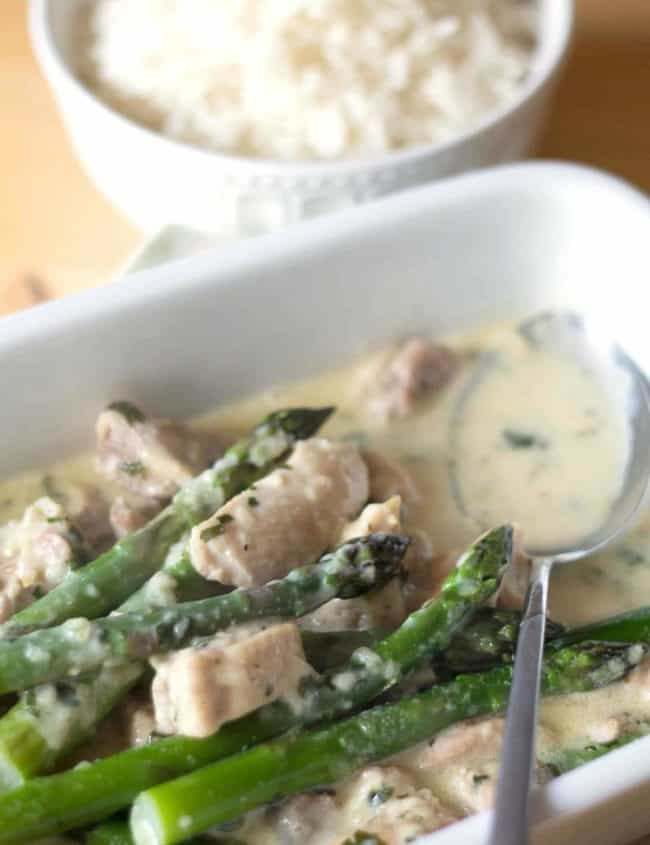 Skinny Creamy Asparagus Chicken in a serving dish with a spoon to serve