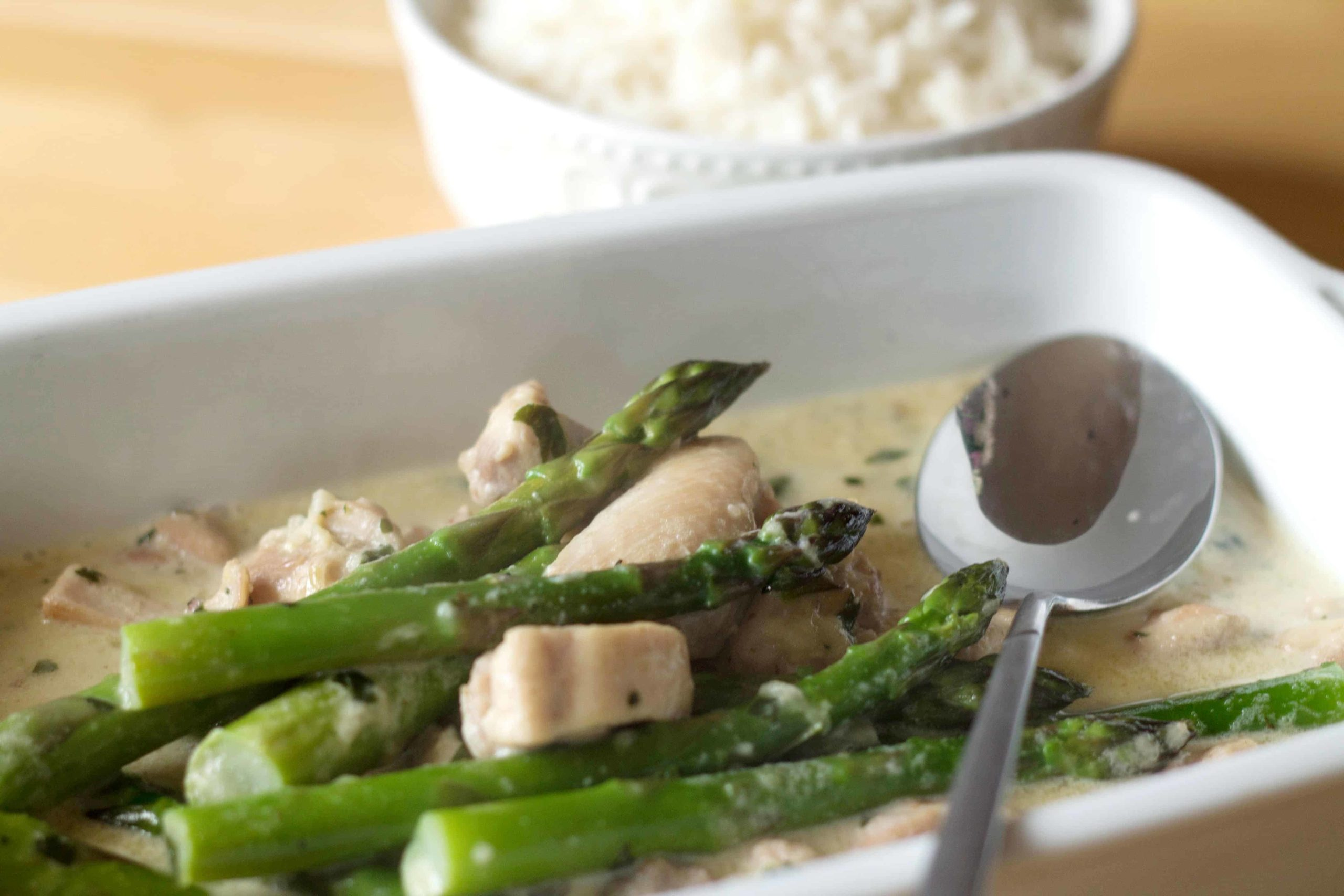 Skinny Creamy Asparagus Chicken in a rectangle serving dish with a spoon and a white bowl of rice in the background