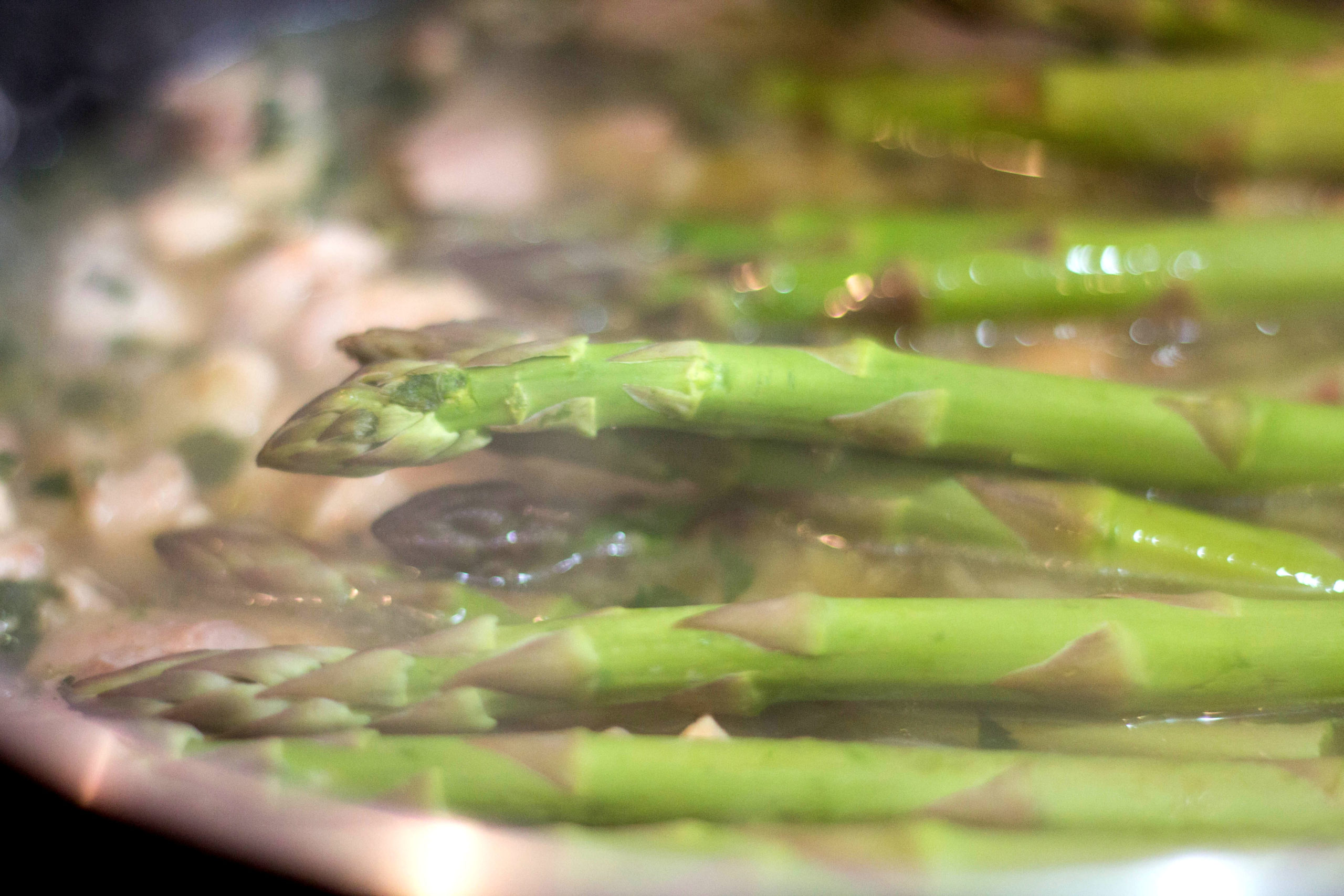 asparagus added to a pan of chicken in stock with herbs