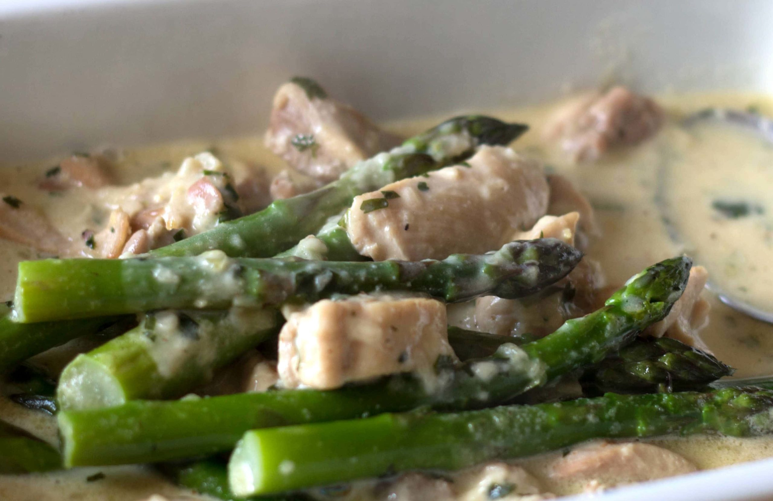 Skinny Creamy Asparagus Chicken in a serving dish with the cream added