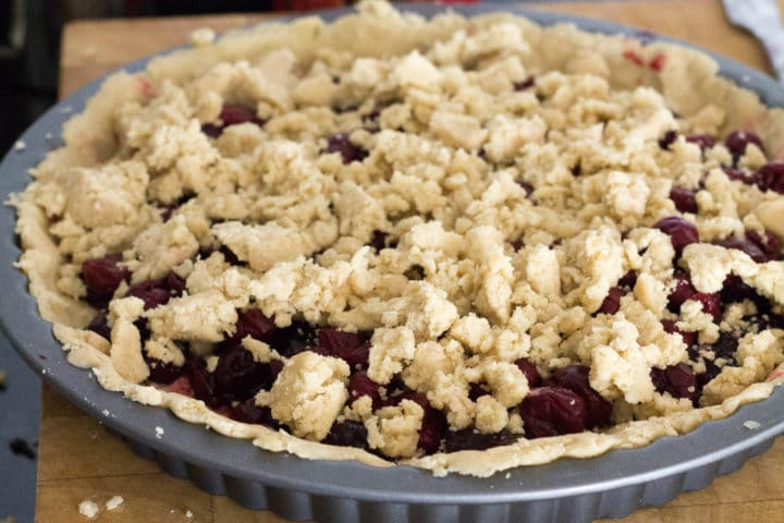 uncooked cherry tart with crumbled topping ready to go in the oven