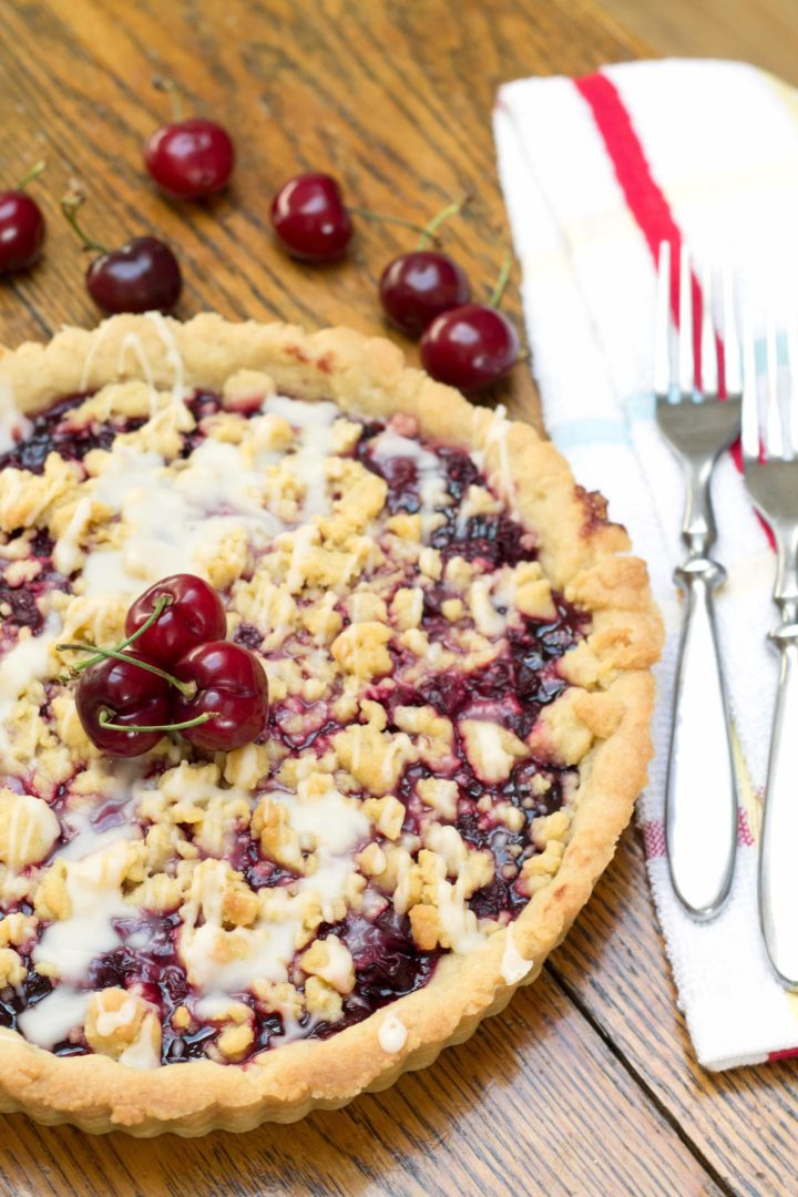 Cherry Vanilla Shortbread Tart with cutlery and fresh cherry garnish