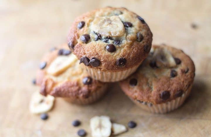 Three Chocolate Chip Banana Muffins stacked on top each other with the top one in focus