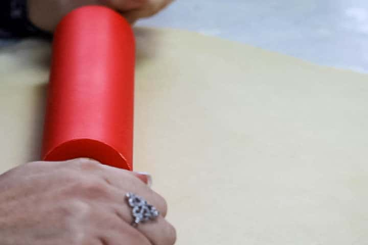 The dough being rolled out with a rolling pin