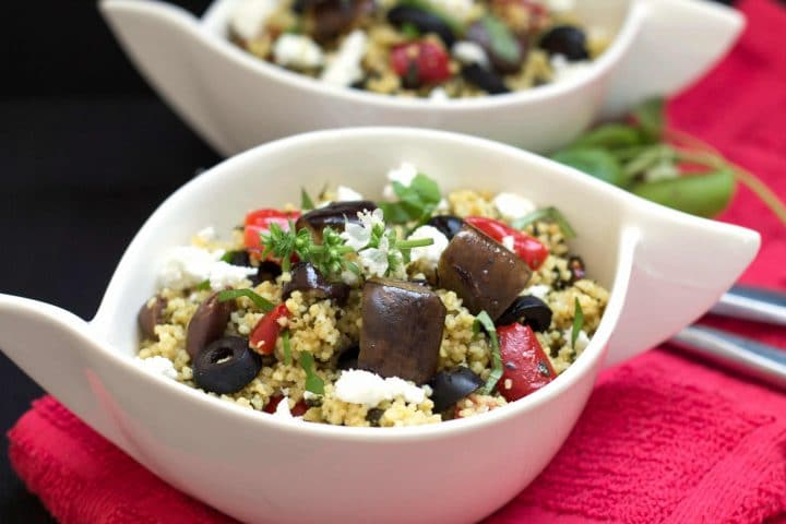 A bowl full of Roasted Eggplant Couscous Salad with black olives, roasted red peppers and feta cheese