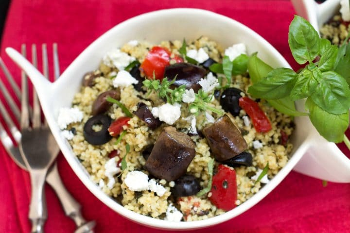 A close up of a bowl filled with couscous, roasted eggplant, sliced black olives, red peppers, and crumbled feta cheese.
