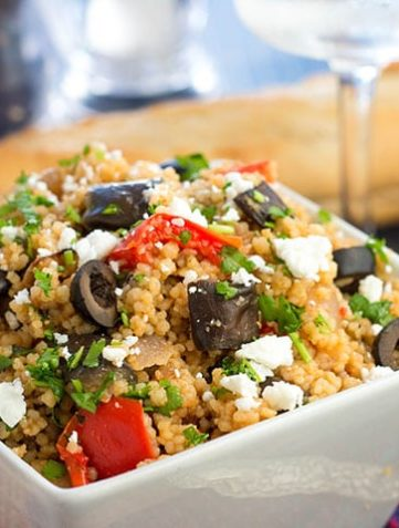 Mediterranean Couscous Salad with Roasted Eggplant in a bowl with a loaf a bread and wine glass on the table in the background