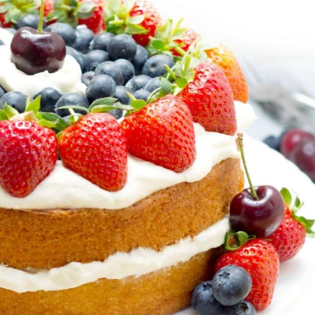 Vanilla Cream Sponge Cake topped with whipped cream and fresh berries