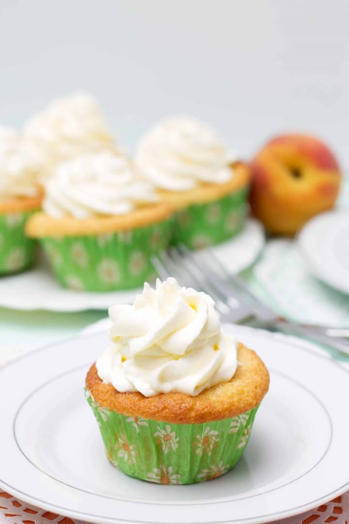 One Peaches and Cream Cupcake on a plate piled high with whipped cream frosting with more cupcakes in the background