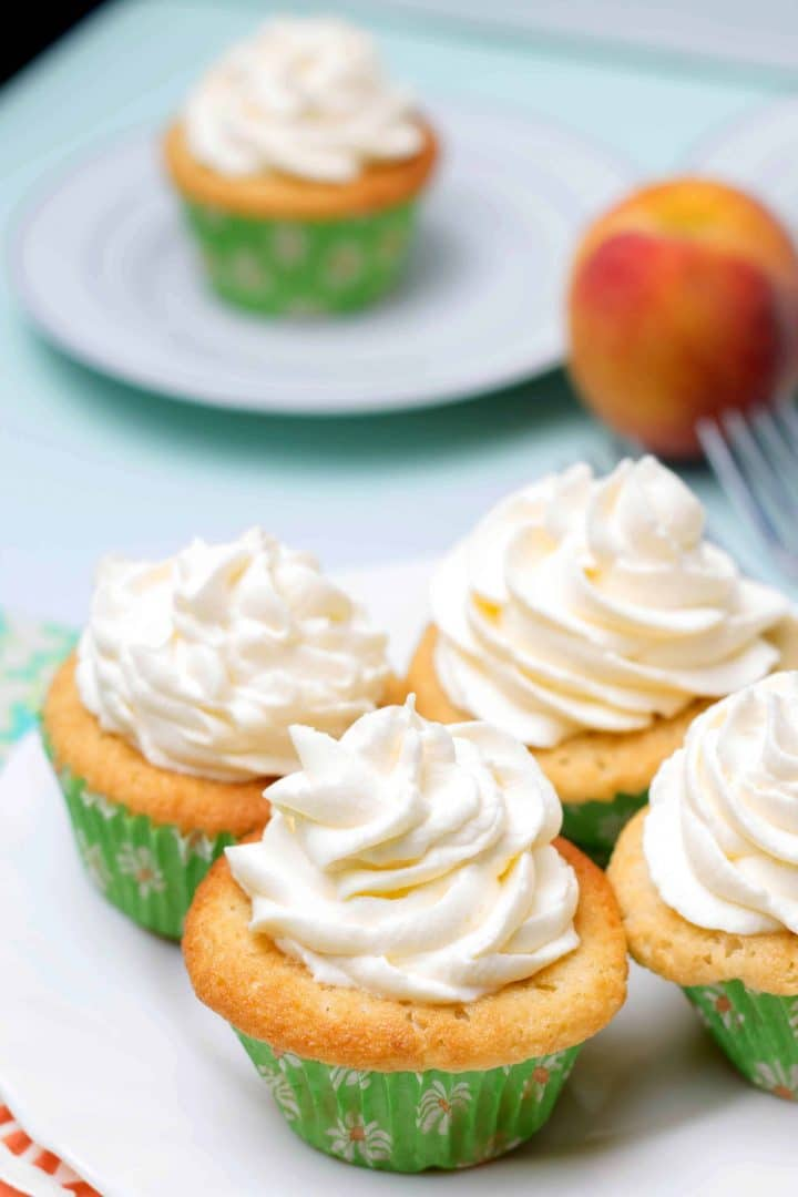 Four Peaches and Cream Cupcake on a serving plate piled high with whipped cream frosting with a peach in the background