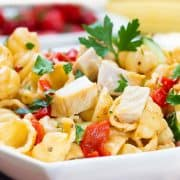 pasta salad with chicken, peppers and herbs in a white bowl