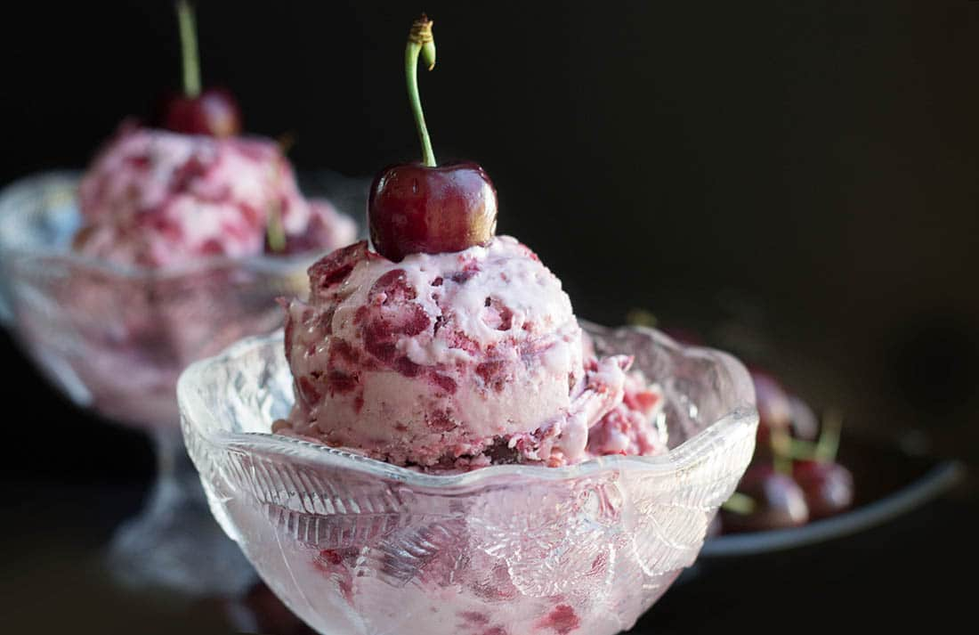 Cherry Ice cream in a pretty glass bowl topped with a fresh cherry.