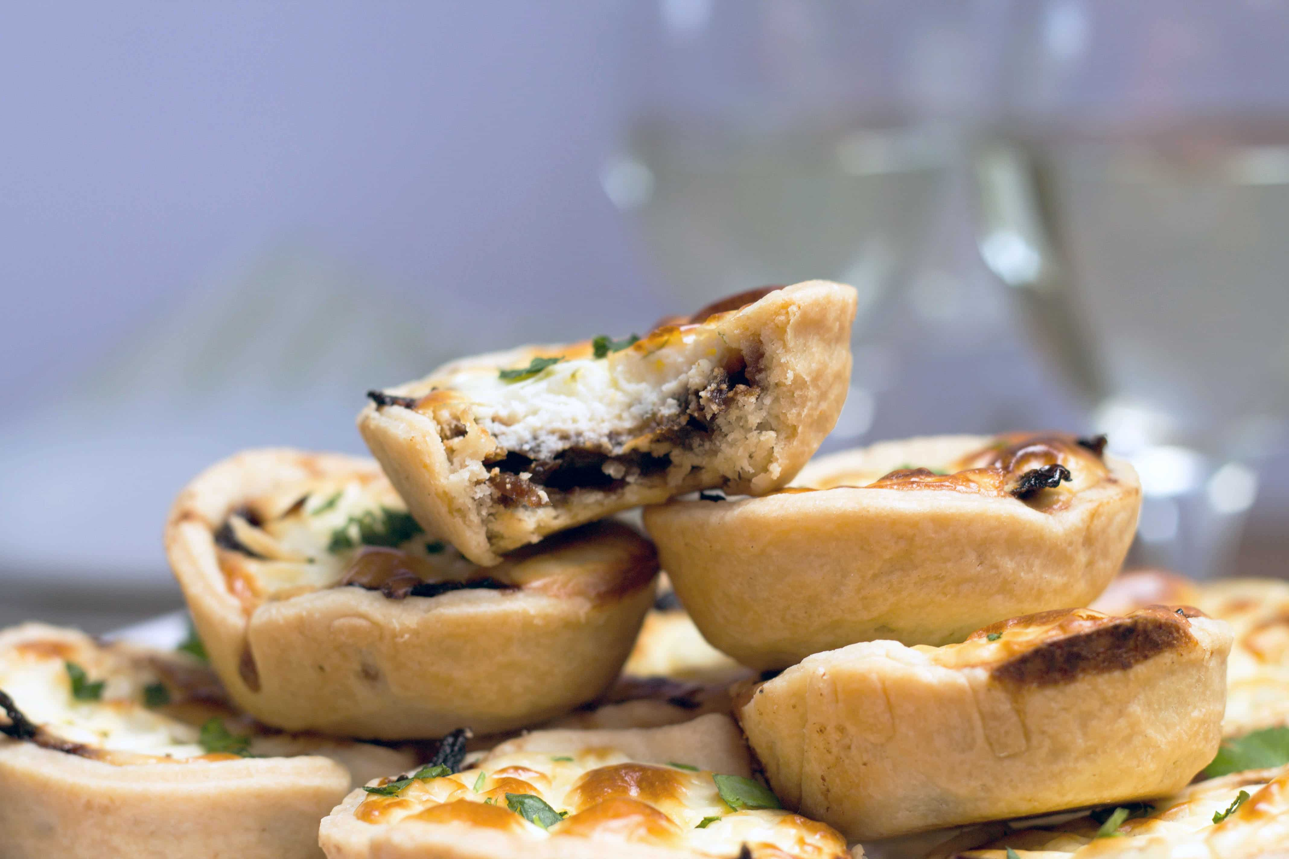 Red Onion & Feta Tarts - one with a bite taken out of it showing the gorgeous filling.