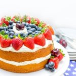 Vanilla Cream Sponge Cake on a cake plate topped with fresh berries