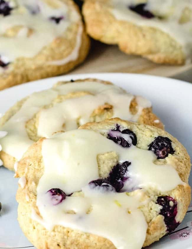 blueberry lemon scones iced, on a plate with more scones in the background