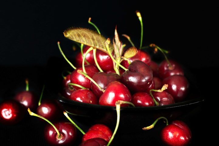 cherries in a black bowl with a black background
