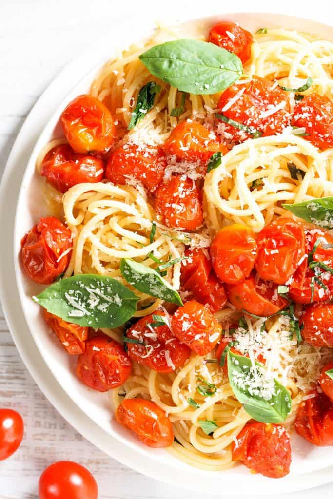 spaghetti with roasted cherry tomato and fresh basil in a white plate