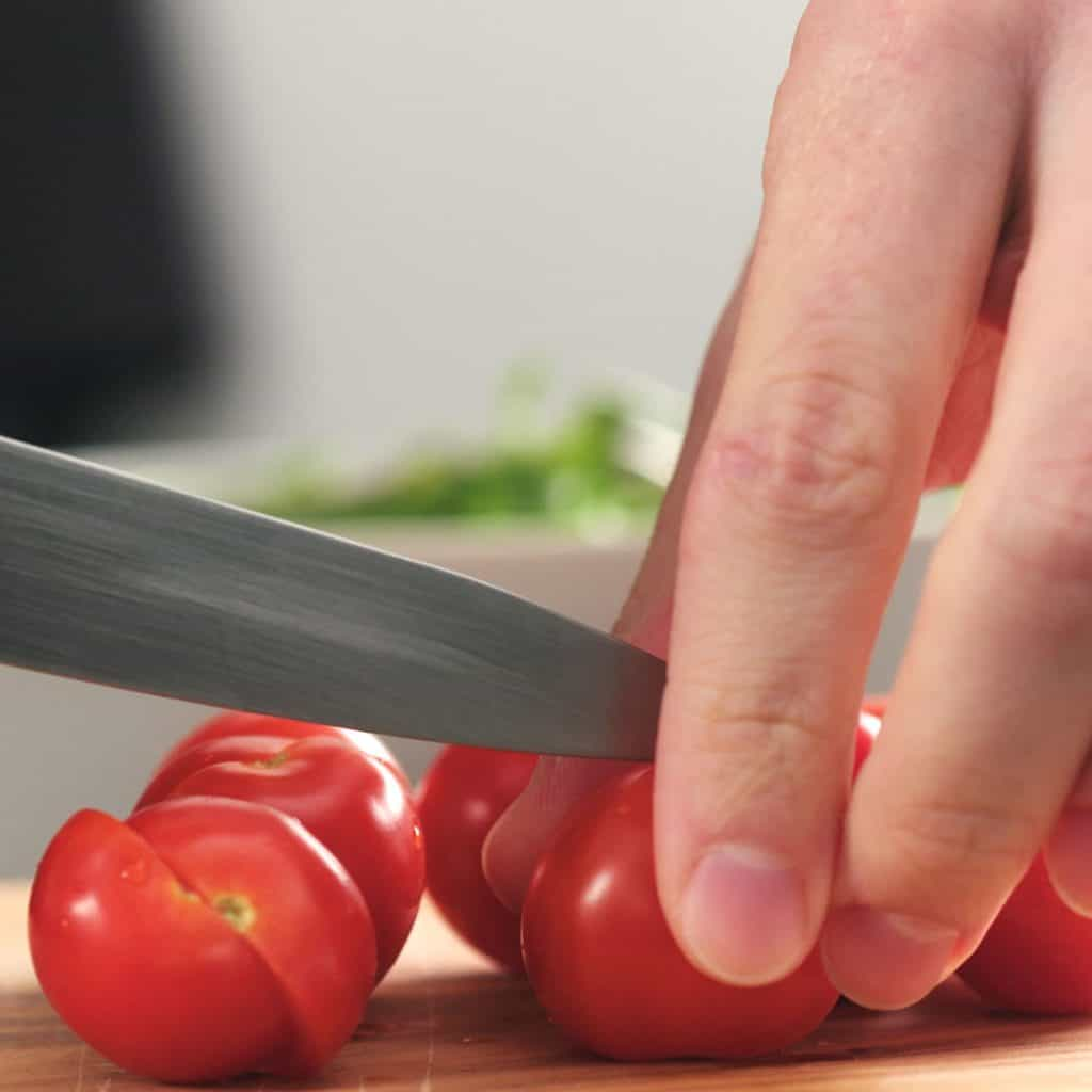 closeup man cutting cherry tomatoes on a cutting board