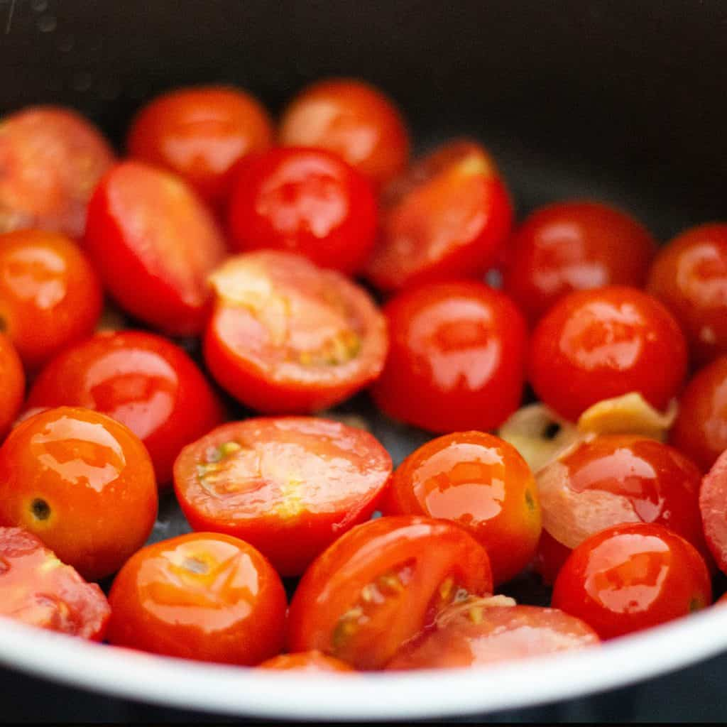 cherry tomatoes added to the pan with the garlic
