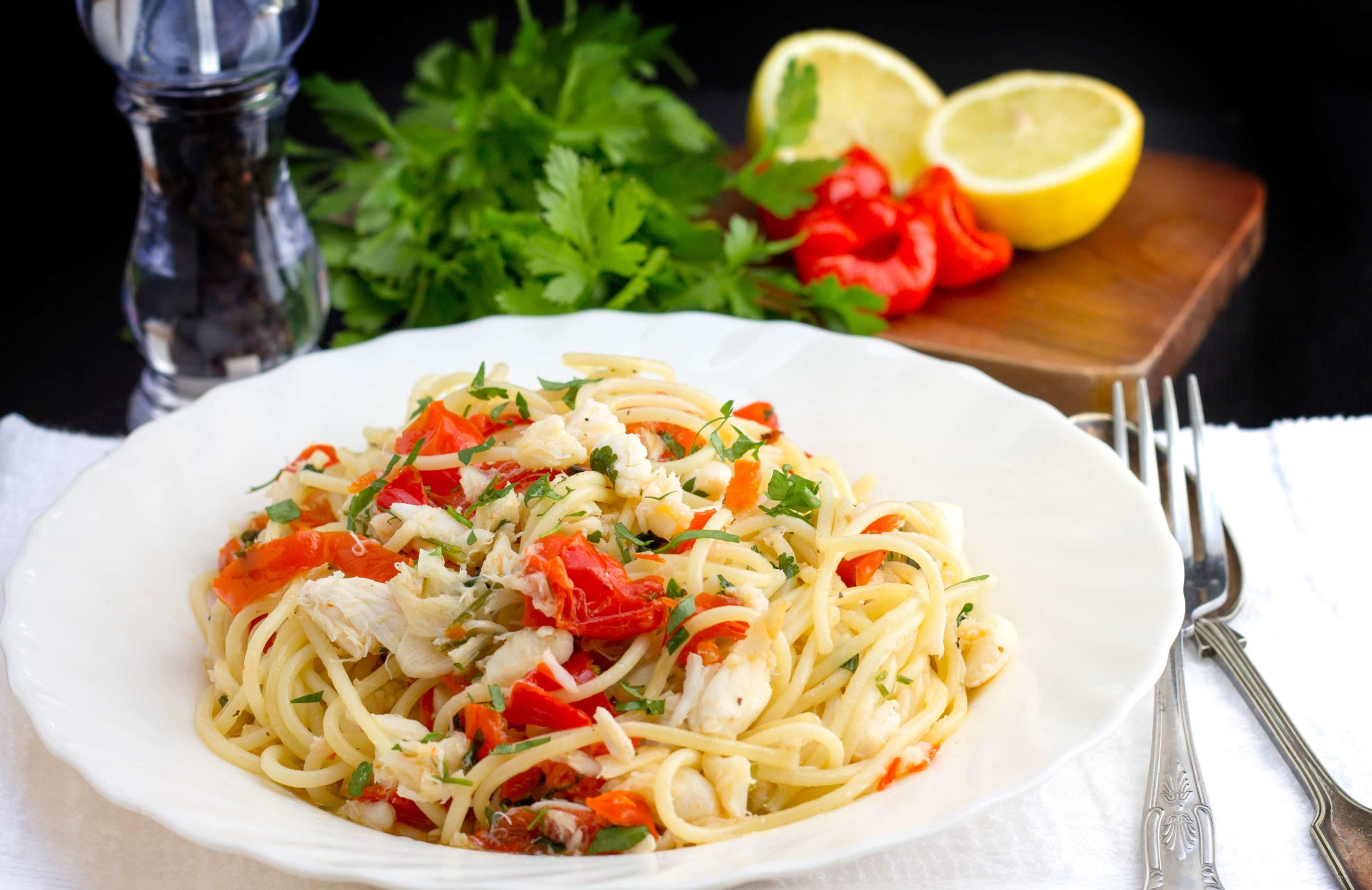 Simple Spaghetti with Crab & Piquante Peppers in a white bowl with cutlery