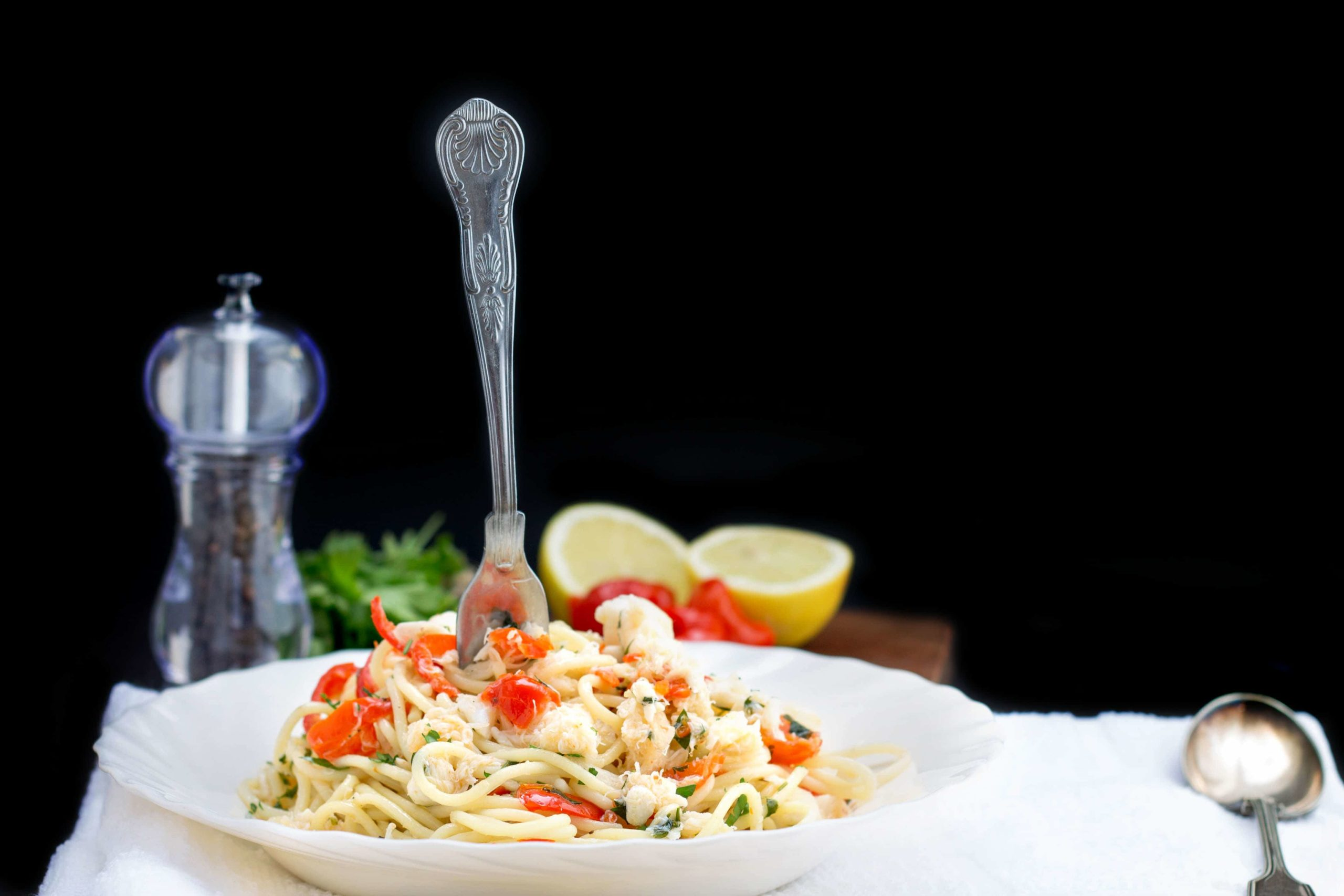 Simple Spaghetti with Crab & Piquante Peppers on a white dish with a fork standing up in the middle of it, with a pepper mill and halved lemon in the background