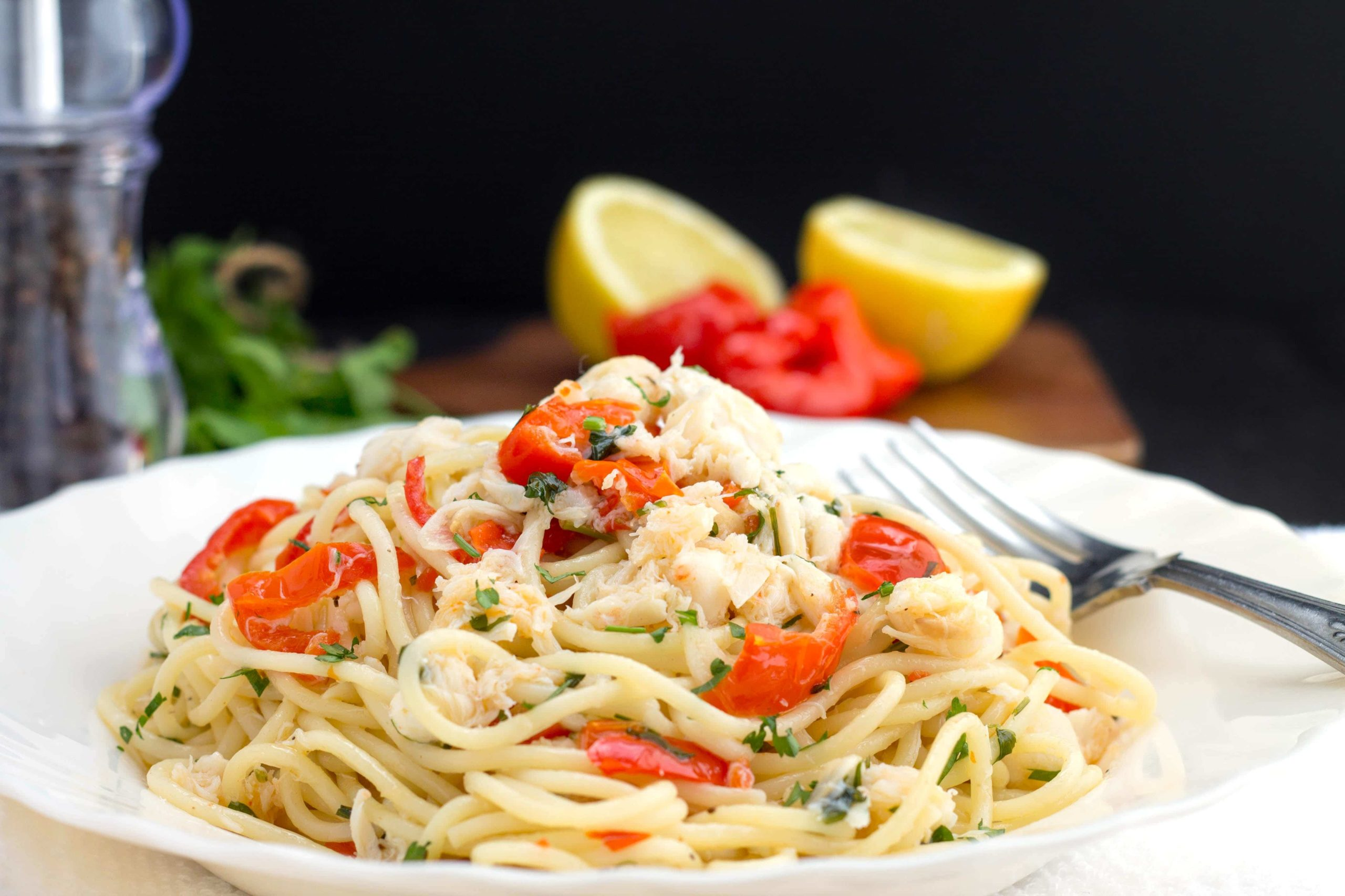 Simple Spaghetti with Crab & Piquante Peppers on a white plate with cutlery